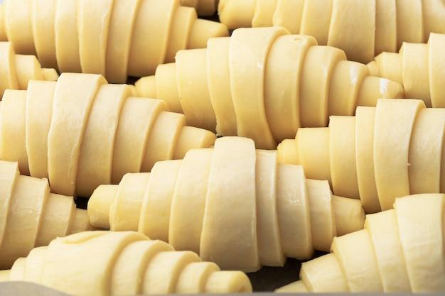Закройте слой пушистых закваски сырых традиционных французских круассанов рулет из теста в противне и листе бумаги, готовясь готовить в духовке. это маслянистое слоеное тесто.