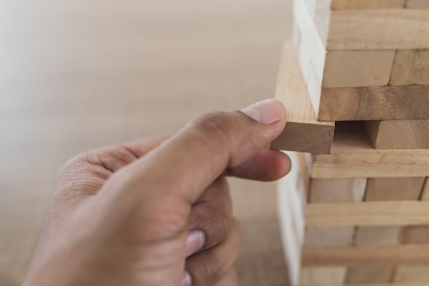 Close up of left hand of man take the wooden stick out of the wooden tower (jenga) side view