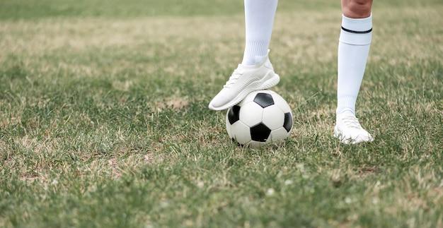 Нога крупным планом на футбольном мяче