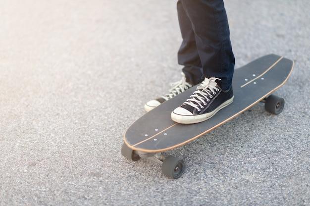 サーフスケートの脚をクローズアップするか、スケートパークのエクストリームスポーツのスケートボード。