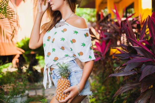クローズアップの脚と腰のスリムなボディは、デニムのショートパンツで裸足で麦わら帽子をかぶった休暇中の魅力的な女性の日焼けした肌をプリントしたtシャツの夏のファッション、パイナップルを持った手