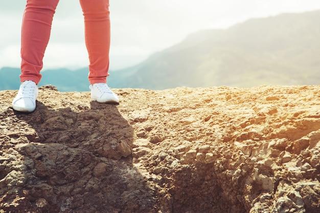Закройте ноги и обувь путешественника, отдыхающего хипстером молодого человека, стоящего на вершине каменного холма высокой горы, наслаждаясь прекрасным захватывающим видом на лес. концепция праздников свободы путешествия.