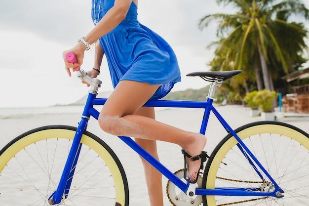 Chiuda sulle gambe della donna attraente in vestito blu che cammina sulla spiaggia tropicale con la bicicletta