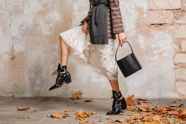 Chiudere le gambe con gli stivali di donna alla moda in giacca che cammina contro il muro in strada