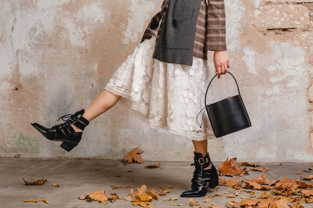 Close up legs in boots of stylish woman in jacket walking against wall in street