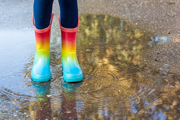 Close up of legs of child girl with rainbow rubber boots jump in puddle on an autumn walk.