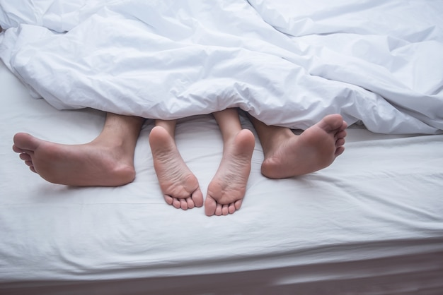 Close up legs of couple in bed