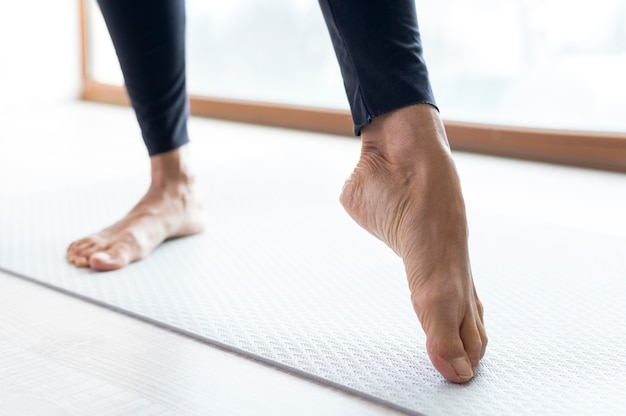 Close-up legs doing stretching exercises before workout
