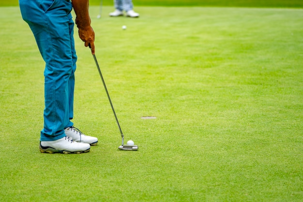 Close up legs and golf club of golfer for putting ball to hole