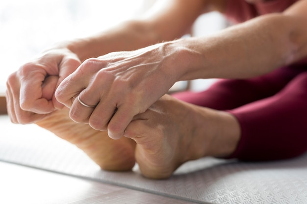 Close-up legs and hands doing stretching exercises