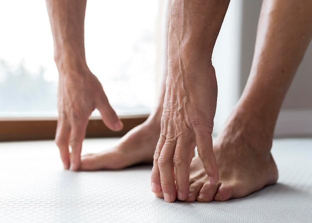 Gambe e mani del primo piano di un uomo anziano