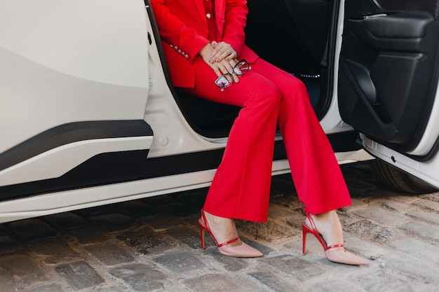 Close up legs in heels and hands holding glasses of beautiful sexy rich business woman in red suit posing in white car