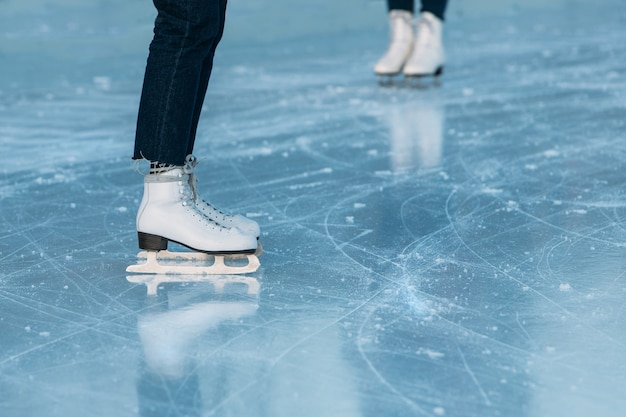 Close up of legs of ice skater on outdoor ice rink.