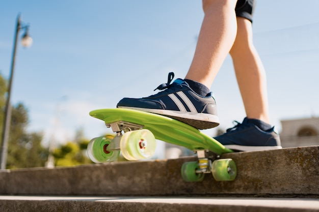 모션에서 녹색 스케이트 보드를 타고 파란색 운동 화에 다리를 닫습니다. 청소년, 훈련, 취미, 활동의 활동적인 도시 생활. 아이들을위한 활동적인 야외 스포츠. 어린이 스케이트 보드.