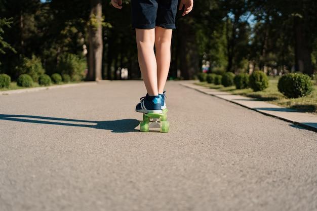 モーションで緑のスケートボードに乗って青いスニーカーで足を閉じます。若者のアクティブな都会のライフスタイル、トレーニング、趣味、活動。子供のためのアクティブなアウトドアスポーツ。子供のスケートボード。
