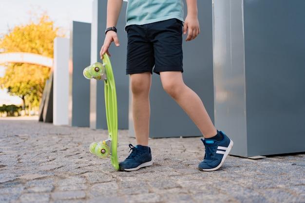 緑のスケートボードと青いスニーカーで足を閉じます。若者のアクティブな都会のライフスタイル、トレーニング、趣味、活動。子供のためのアクティブなアウトドアスポーツ。子供のスケートボード。