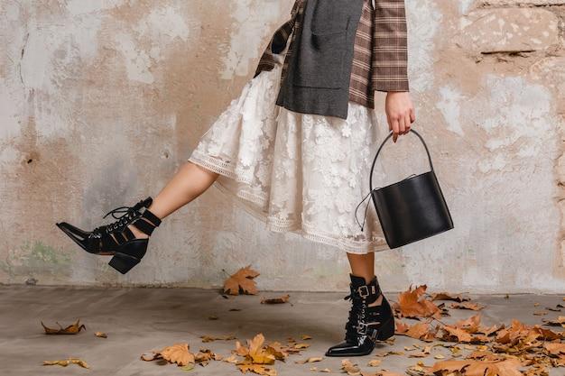 Крупным планом ноги в сапогах стильной женщины в куртке, идущей против стены на улице