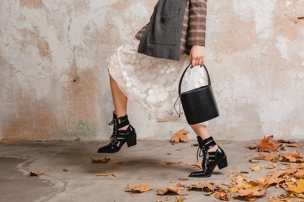 거리에서 벽에 걸어 재킷에 세련된 여성의 부츠에 다리를 닫습니다