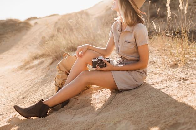 靴で足を閉じ、砂漠でカーキ色のドレスを着たスタイリッシュな女性のファッションの詳細、サファリでアフリカを旅行、ブーツを履いて、バックパックを持っています