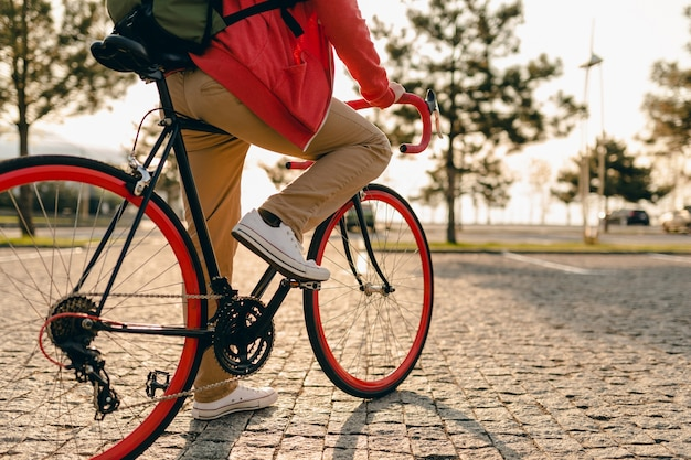 Крупным планом ноги в кроссовках и руки на рулевом колесе бородатого мужчины в стиле хипстера в красной толстовке с капюшоном и бежевых брюках, едущего в одиночестве с рюкзаком на велосипеде, здоровый активный образ жизни, путешественник с рюкзаком