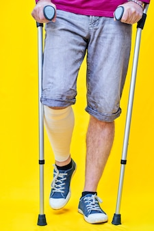 Close-up of the legs of a man from the front with shorts and crutches, with a bandaged leg.