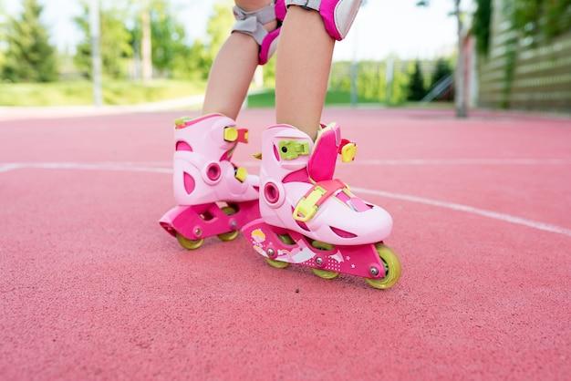 公園でスケートをしている女の子のローラースケートのクローズアップ脚