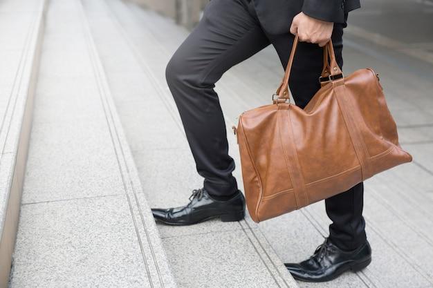 계단을 올라가는 계단 사람을 스테핑 걷는 사업가의 다리를 닫습니다. 새로운 시작에서 자신있게 앞으로 나아갑니다. 비즈니스 개념을 자랍니다.