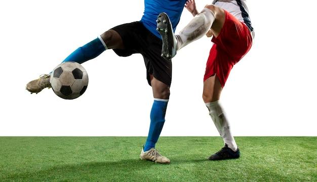 흰색 배경에 격리된 필드에서 공을 놓고 싸우는 축구 선수, 프로 축구의 다리를 닫습니다. 게임 중 액션, 모션, 높은 긴장된 감정의 개념. 자른 이미지.