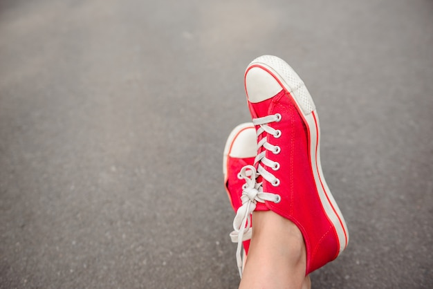 Close up of legs in red keds lying on asphalt.