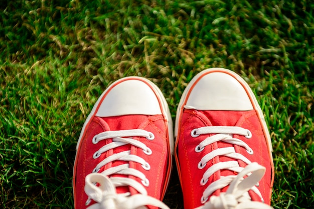 Close up of legs in red keds lying on grass.