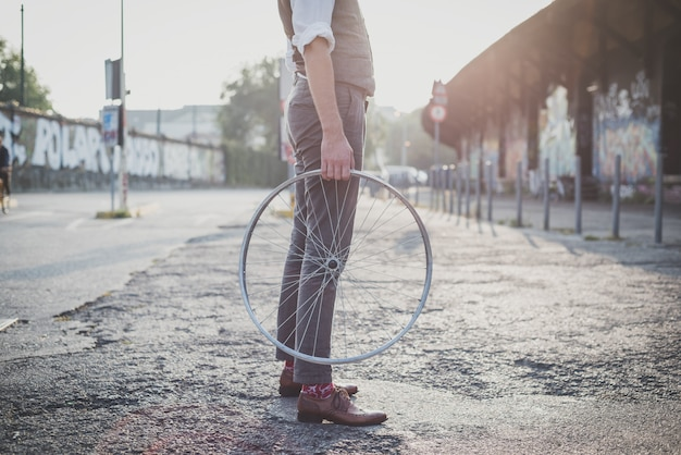 Close up of legs shoes hipster man holding old bicycle wheel