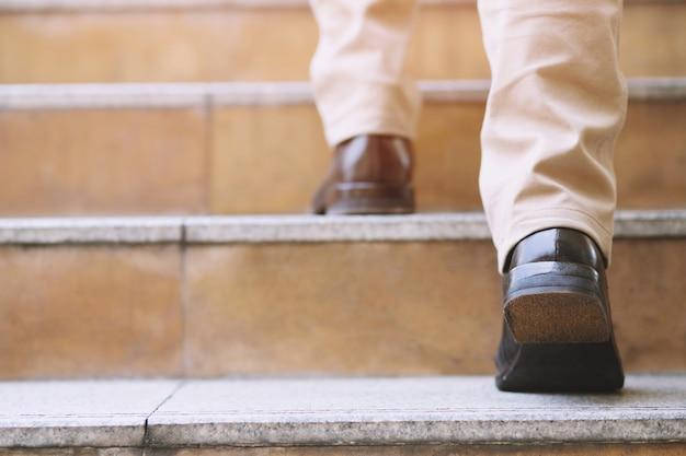 若いビジネスマンの足の靴をクローズアップ現代の街の階段を上って歩いて、上がって、成功して、成長する一人。フィルタートーンレトロヴィンテージウォームエフェクト付き。階段