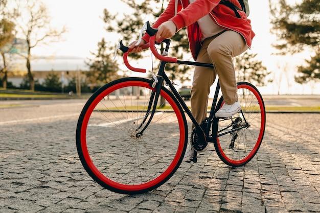 Chiudere le gambe in scarpe da ginnastica e le mani sul volante dell'uomo barbuto stile hipster in felpa con cappuccio rossa e pantaloni beige cavalcando da solo con lo zaino in bicicletta viaggiatore zaino in spalla sano stile di vita attivo