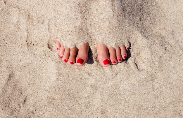 Close up legs of tanned woman with clear sand