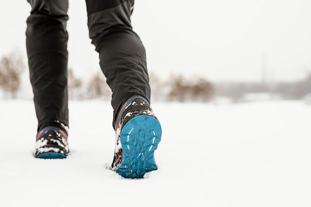 Крупным планом ноги, идущие в снегу