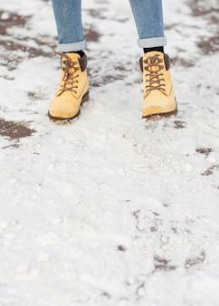 Gambe di primo piano che indossano stivali invernali