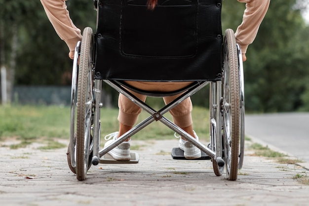 Close-up of legs in a wheelchair. the girl is disabled. the concept of a wheelchair, disabled person, full life, paralyzed, disabled person, health care.