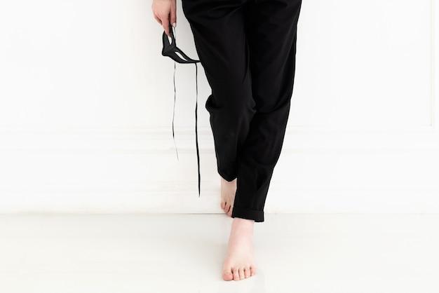 흰 벽 근처에 서서 끈으로 검은 카니발 마스크를 들고 검은 바지를 입은 젊은 여성의 맨발로 다리를 닫습니다