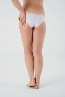 Close up on legs of woman in basic underwear isolated