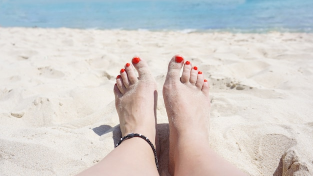 Close up of legs. woman relaxing in sea while spending summer day at the beach.