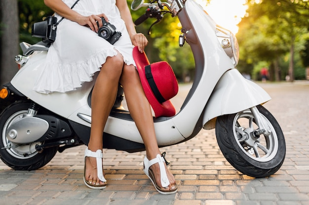 Close up legs of woman sitting on motorbike in street, summer vacation style, traveling, stylish outfit, adventures, holding vintage photo camera, footwear, tanned legs in sandals sandals, red hat