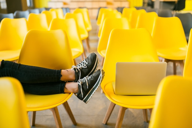 Close up legs of young stylish woman sitting in lecture hall with laptop, classroom with many yellow chairs, footwear sneakers, shoes fashion trend