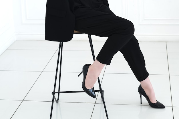 Close up legs of young woman in black business suit and high-heeled shoes sits on the stool