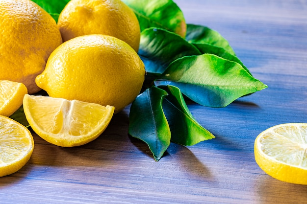 Close up of lemon and green leaves on rustic wooden table