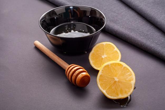 Close-up lemon slices and honey stick