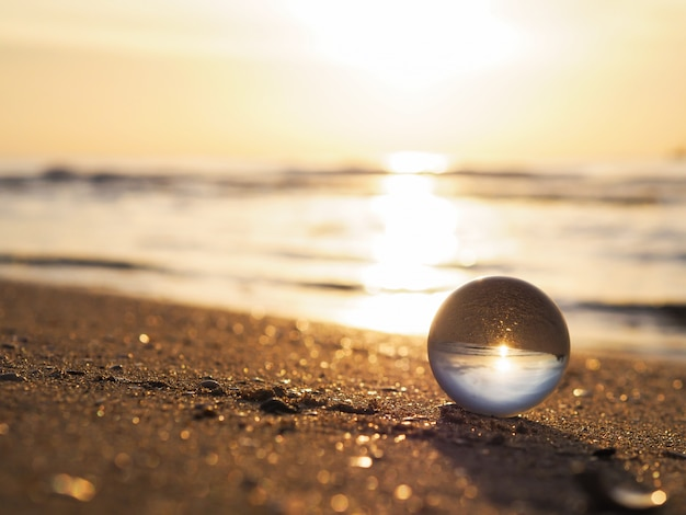 Close up lens ball with golden sunrise reflection at summer beach.