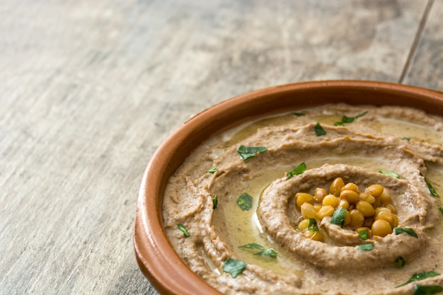 Close up lentil hummus in bowl on wood