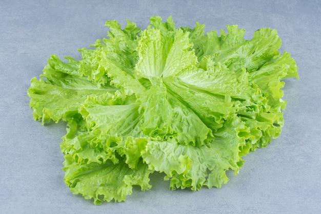 Закройте листья салата на сером фоне.