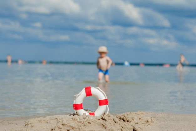 Close-up of lifebuoy on the beach on baby background. safety on the water.