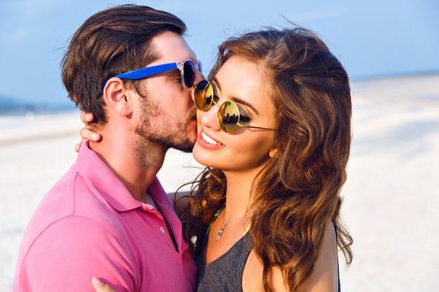 サングラスを身に着けている魅力的な若い流行に敏感なカップル、ライフスタイルファッションの肖像画をクローズアップ、ハンサムな男が彼のブルネットのガールフレンドの頬にキス、ビーチで幸せな日。